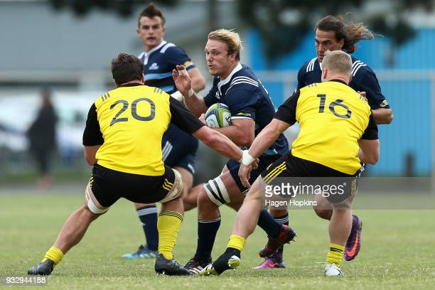 Matt Matich of the Blues A Team runs at Will Mangos and James O'Rielly of the Hurricanes during the development squad trial match between the...