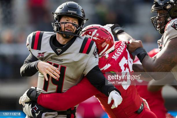 Matt McGloin of the NY Guardians is hit by Jonathan Massaquoi of the DC Defenders during the first half of the XFL game at Audi Field on February 15...