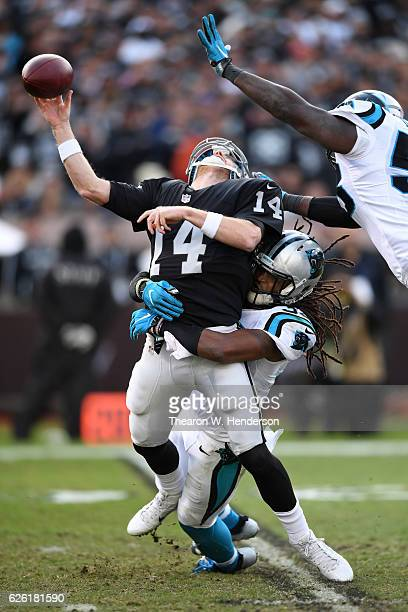 Matt McGloin of the Oakland Raiders is hit by Tre Boston of the Carolina Panthers during their NFL game on November 27 2016 in Oakland California