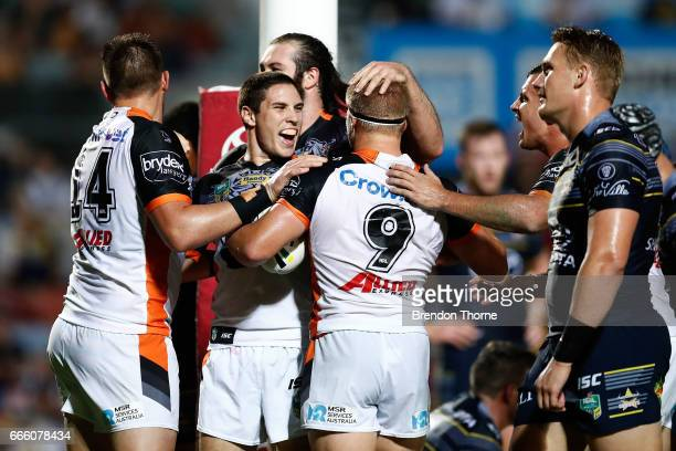Matt McIlwrick of the Tigers celebrates with team mate Mitchell Moses after scoring a try during the round six NRL match between the North Queensland...