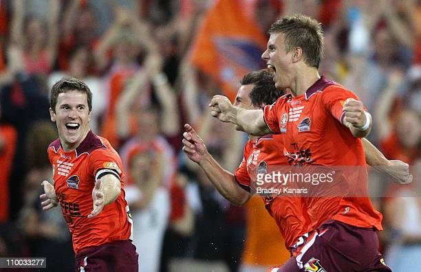 Matt McKay , and Erik Paartalu of the Roar celebrate victory after the A-League Grand Final match between the Brisbane Roar and the Central Coast...
