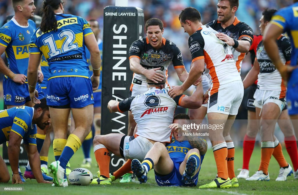 Matt Mcllwrick of the Tigers celebrates scoring a try with team mates during the round seven NRL match between the Parramatta Eels and the Wests Tigers at ANZ Stadium on April 17, 2017 in Sydney, Australia.