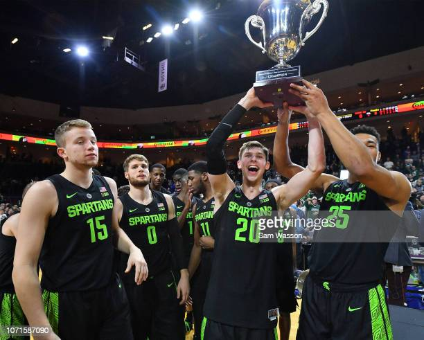 Matt McQuaid and Kenny Goins of the Michigan State Spartans hold up the championship trophy after winning the championship game of the 2018...