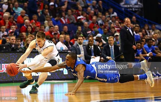 Matt McQuaid of the Michigan State Spartans and Jaqawn Raymond of the Middle Tennessee Blue Raiders compete for a loose ball in the first half during...