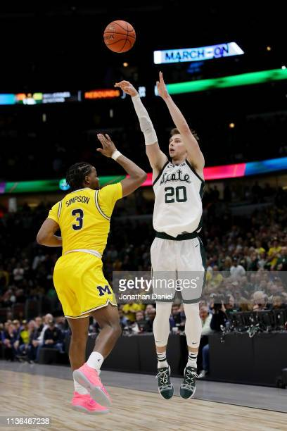 Matt McQuaid of the Michigan State Spartans attempts a shot while being guarded by Zavier Simpson of the Michigan Wolverines in the second half...