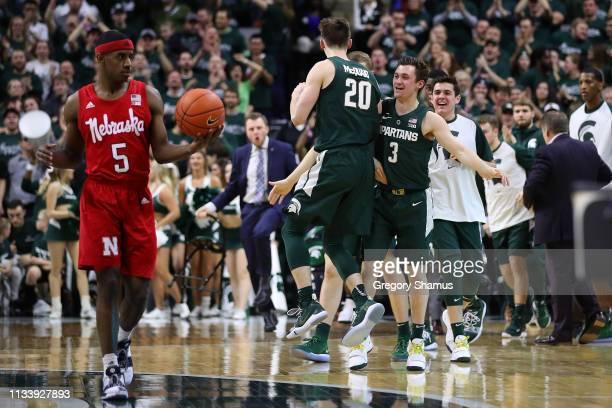 Matt McQuaid of the Michigan State Spartans celebrates a second half three point basket with teammates behind Glynn Watson Jr #5 of the Nebraska...
