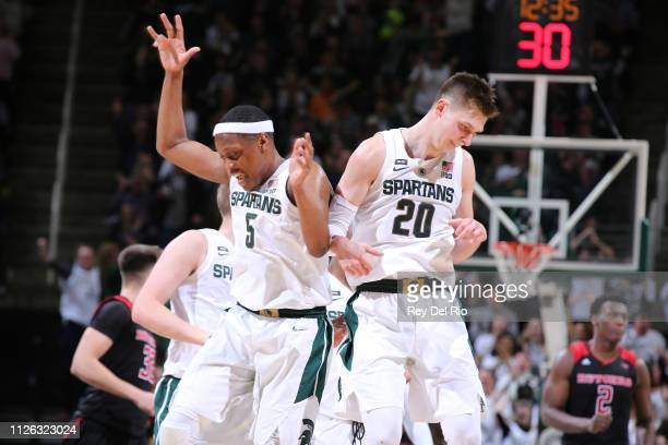 Matt McQuaid of the Michigan State Spartans celebrates his threepoint basket in the second half with teammate Cassius Winston of the Michigan State...