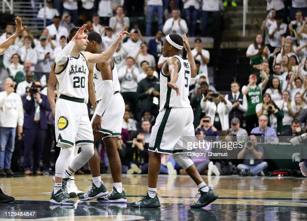Matt McQuaid of the Michigan State Spartans celebrates with Cassius Winston after defeating the Michigan Wolverines 7563 at Breslin Center on March 9...