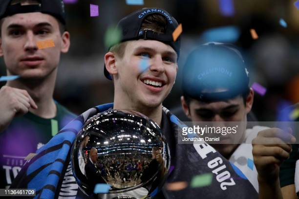 Matt McQuaid of the Michigan State Spartans celebrates with the trophy after beating the Michigan Wolverines 6560 in the championship game of the Big...