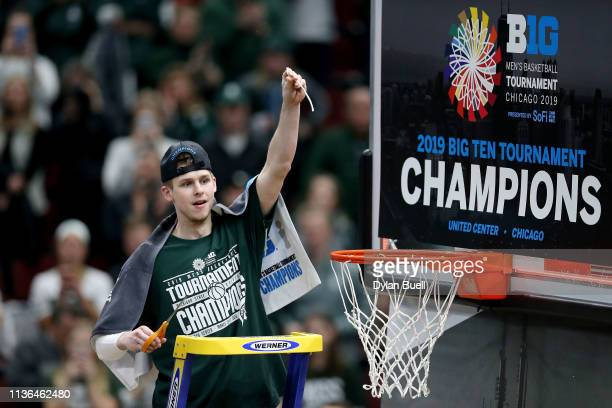 Matt McQuaid of the Michigan State Spartans cuts down the net after beating the Michigan Wolverines 6560 in the championship game of the Big Ten...