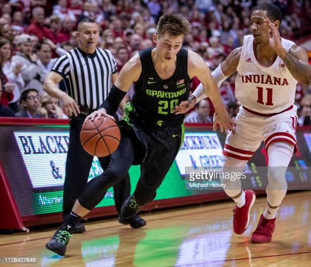 Matt McQuaid of the Michigan State Spartans dribbles the ball around Devonte Green of the Indiana Hoosiers at Assembly Hall on March 2 2019 in...