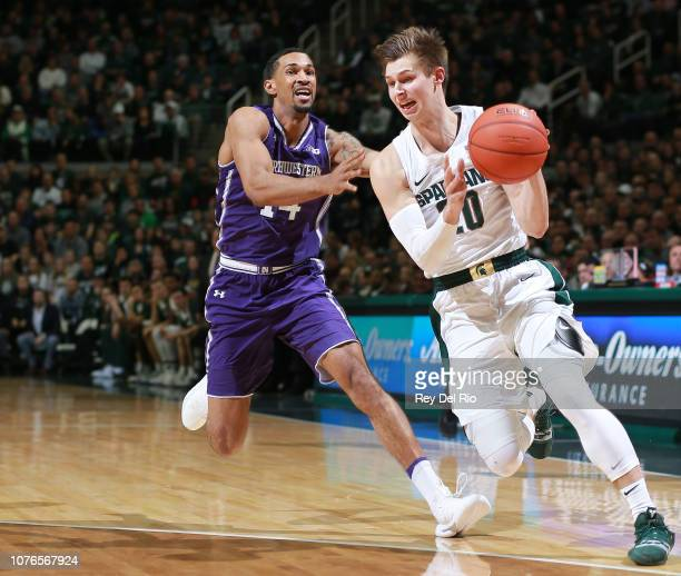 Matt McQuaid of the Michigan State Spartans drives past Ryan Taylor of the Northwestern Wildcats in the first half at Breslin Center on January 2...