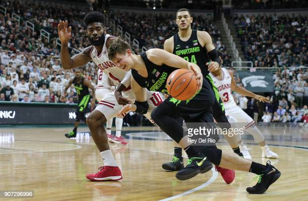 Matt McQuaid of the Michigan State Spartans drives to the basket and draws a foul from Robert Johnson of the Indiana Hoosiers at Breslin Center on...