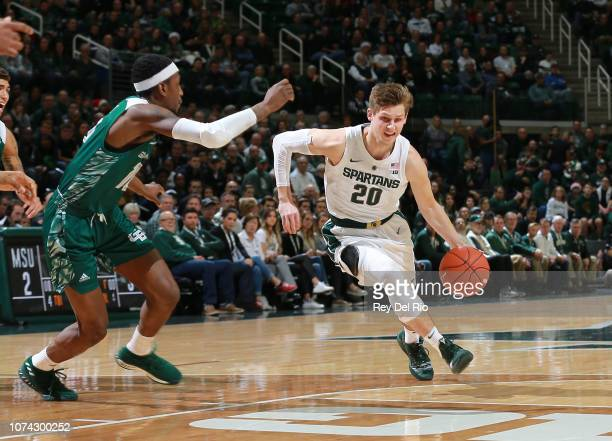 Matt McQuaid of the Michigan State Spartans drives to the basket while defended by Shanquan Hemphill of the Green Bay Phoenix at Breslin Center on...