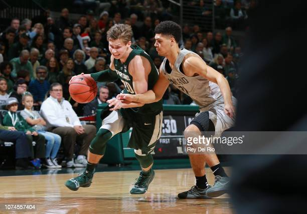 Matt McQuaid of the Michigan State Spartans drives to the basket while defended by Jaevin Cumberland of the Oakland Golden Grizzlies in the first...