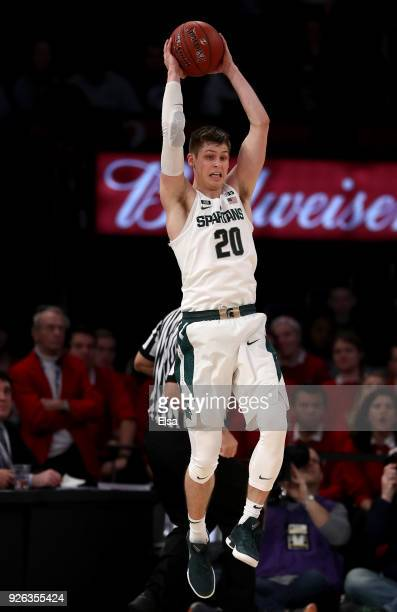 Matt McQuaid of the Michigan State Spartans leaps to catch a high flying pass in the first half against the Wisconsin Badgers during quarterfinals of...