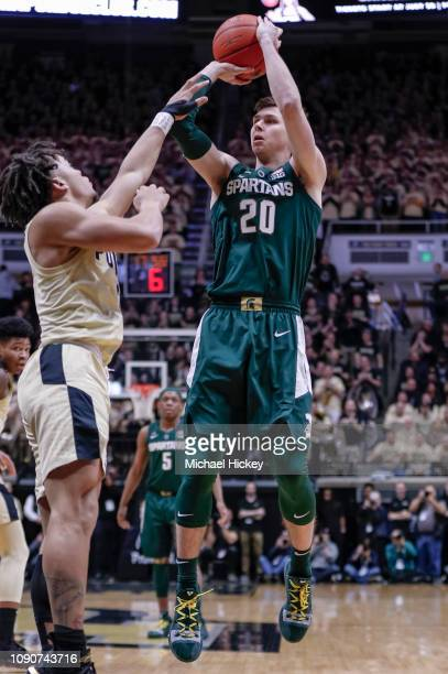 Matt McQuaid of the Michigan State Spartans shoots the ball against Carsen Edwards of the Purdue Boilermakers at Mackey Arena on January 27 2019 in...