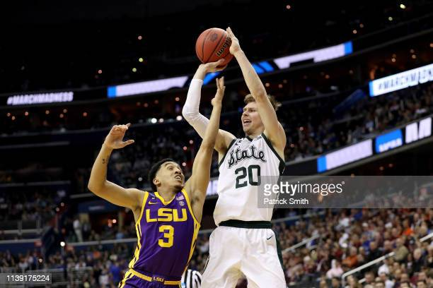 Matt McQuaid of the Michigan State Spartans shoots the ball against Tremont Waters of the LSU Tigers during the first half in the East Regional game...