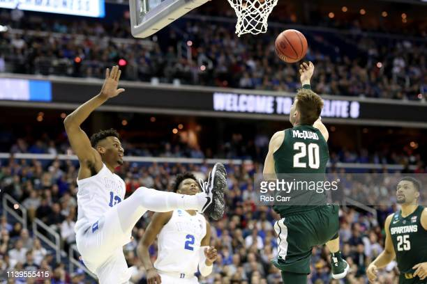 Matt McQuaid of the Michigan State Spartans shoots the ball against Javin DeLaurier of the Duke Blue Devils during the second half in the East...