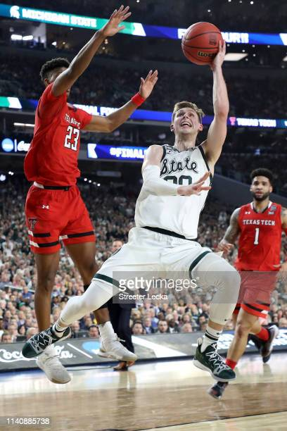 Matt McQuaid of the Michigan State Spartans shoots the ball against Jarrett Culver of the Texas Tech Red Raiders in the first half during the 2019...