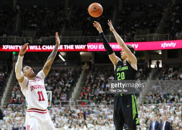 Matt McQuaid of the Michigan State Spartans shoots the ball over Devonte Green of the Indiana Hoosiers at Breslin Center on January 19 2018 in East...