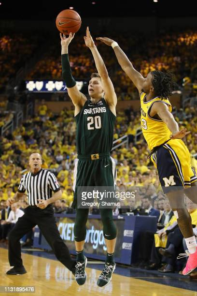 Matt McQuaid of the Michigan State Spartans takes a shot next to Zavier Simpson of the Michigan Wolverines during the second half at Crisler Arena on...