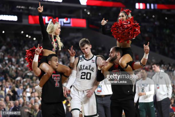 Matt McQuaid of the Michigan State Spartans walks past Texas Tech Red Raiders cheerleaders after being defeated by the Red Raiders 61-51 during the...