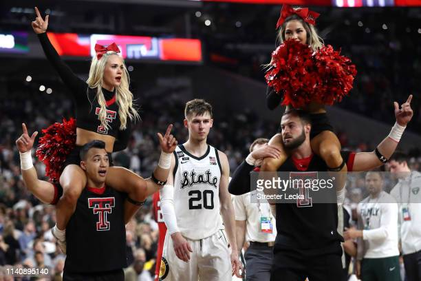 Matt McQuaid of the Michigan State Spartans walks past Texas Tech Red Raiders cheerleaders after being defeated by the Red Raiders 6151 during the...