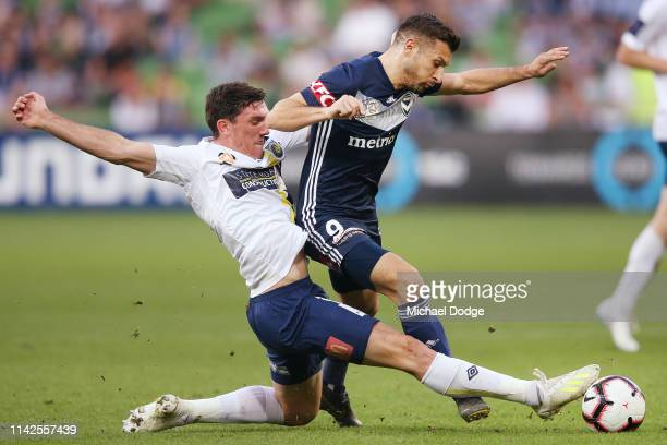 Matt Millar of the Mariners tackles Kosta Barbarouses of the Victory during the round 25 A-League match between Melbourne Victory and the Central...