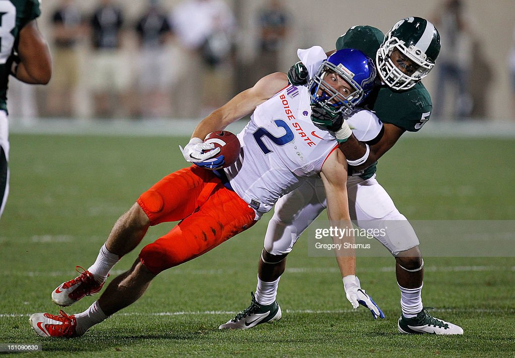 Matt Miller #2 of the Boise State Broncos is tackled after a third quarter catch by Johnny Adams #5 of the Michigan State Spartans at Spartan Stadium on August, 2010 in East Lansing, Michigan. Michigan State won the game 17-13.