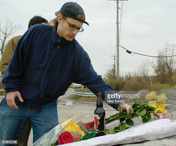 Matt Mitchell places flowers at a makeshift memorial outside the Alrosa Villa nightclub, the day after a gunman fired on the band Damageplan,...