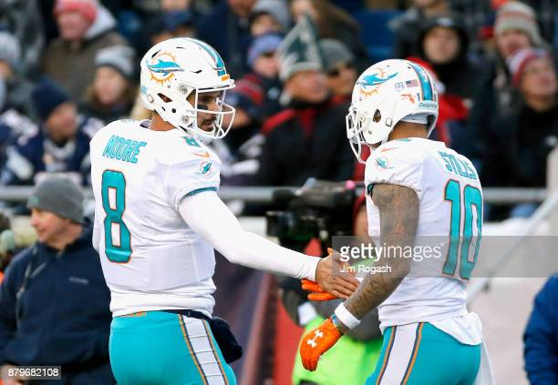 Matt Moore high fives Kenny Stills of the Miami Dolphins during the fourth quarter of a game against the New England Patriots at Gillette Stadium on...