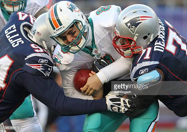 Matt Moore of the Miami Dolphins is sacked by Shaun Ellis of the New England Patriots and teammate Brandon Deaderick in the second half at Gillette...