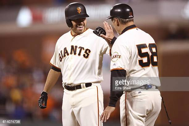 Matt Moore of the San Francisco Giants celebrates with first base coach Bill Hayes after an RBI single in the fourth inning of Game Four of their...