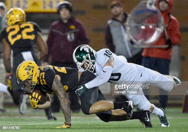 Matt Morrissey of the Michigan State Spartans tackles Shannon Brooks of the Minnesota Golden Gophers during the first quarter of the game on October...
