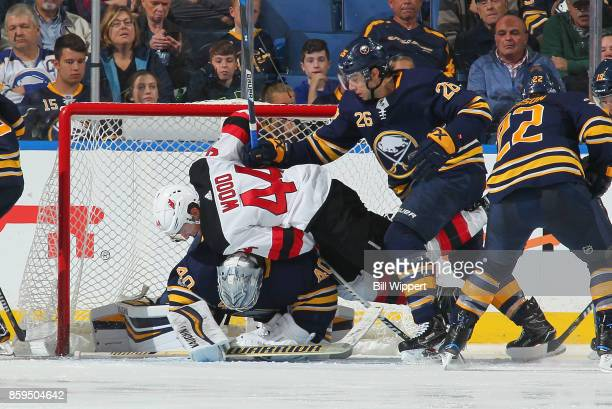 Matt Moulson of the Buffalo Sabres checks Miles Wood of the New Jersey Devils into goaltender Robin Lehner during an NHL game on October 9 2017 at...