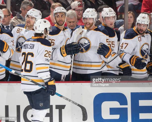 Matt Moulson of the Buffalo Sabres pounds gloves with teammates on the bench following his second period goal during an NHL game against the Detroit...