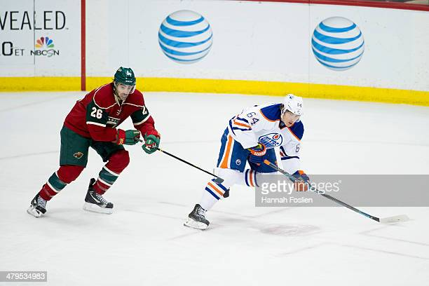 Matt Moulson of the Minnesota Wild and Nail Yakupov of the Edmonton Oilers skate after the puck during the game on March 11 2014 at Xcel Energy...