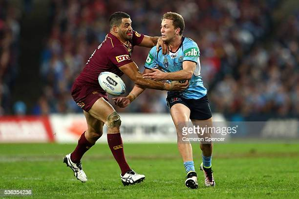 Matt Moylan of the Blues offloads the ball before being tackled by Greg Inglis of the Maroons during game one of the State Of Origin series between...