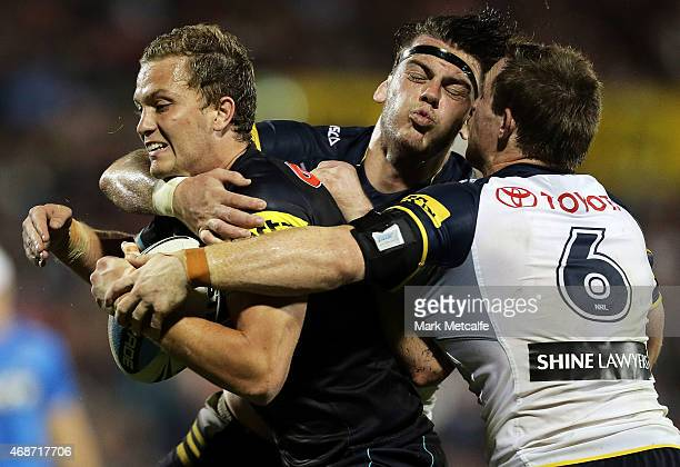 Matt Moylan of the Panthers is tackled by Ethan Lowe and Michael Morgan of the Cowboys during the round five NRL match between the Penrith Panthers...