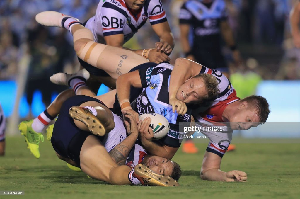 Matt Moylan of the Sharks is tacked by Dylan Napa and Jared Waerea-Hargreaves of the Roosters during the round five NRL match between the Cronulla Sharks and the Sydney Roosters at Southern Cross Group Stadium on April 6, 2018 in Sydney, Australia.