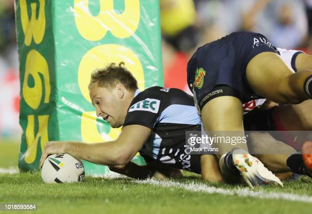 John Asiata of the Cowboys is tackled by Paul Gallen and James Segeyaro of the Sharks during the round 23 NRL match between the Cronulla Sharks and...