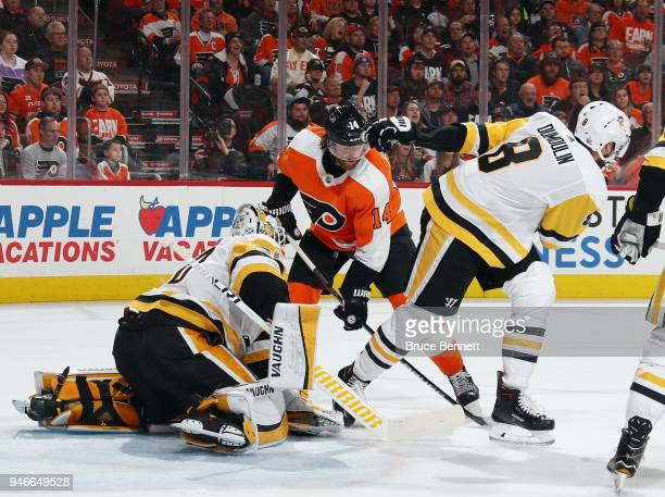 Matt Murray and Brian Dumoulin of the Pittsburgh Penguins defend against Sean Couturier of the Philadelphia Flyers during the second period in Game...