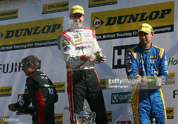 Matt Neal of Great Britain and driver of the Honda YUASA Racing Team Honda Civic sprays champagne and celebrates with second placed Andrew Jordan and...