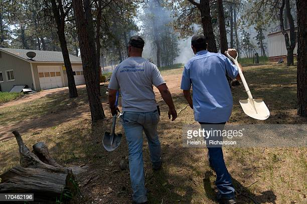 Matt Newland left and friend Chad Mazari take shovels in around neighbors houses to help put out small fires off of Cyprus road in the Black Forest...