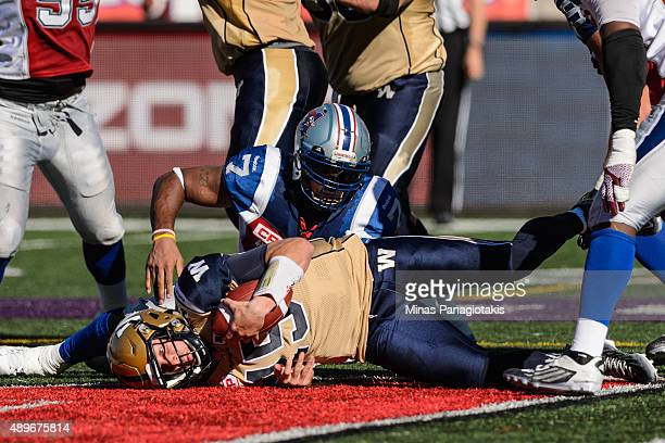 Matt Nichols of the Winnipeg Blue Bombers is sacked by John Bowman of the Montreal Alouettes during the CFL game at Percival Molson Stadium on...