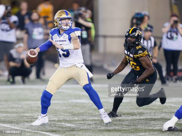 Matt Nichols of the Winnipeg Blue Bombers looks to pass as Ja'Gared Davis of the Hamilton Tiger-Cats applies pressure at Tim Hortons Field on July...