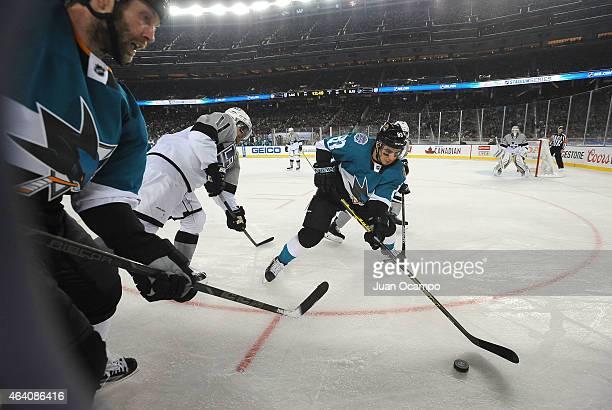 Matt Nieto of the San Jose Sharks plays the puck away from Anze Kopitar and Jamie McBain of the Los Angeles Kings as Joe Thornton of the San Jose...