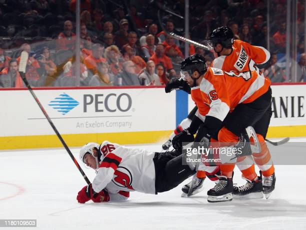 Matt Niskanen and Travis Sanheim of the Philadelphia Flyers trips up Jack Hughes of the New Jersey Devils during the first period at the Wells Fargo...