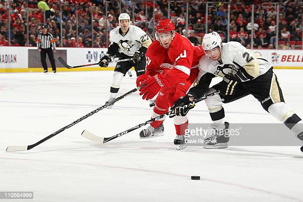 Matt Niskanen of the Pittsburg Penguins battles for the puck with Drew Miller of the Detroit Red Wings during an NHL game at Joe Louis Arena on March...